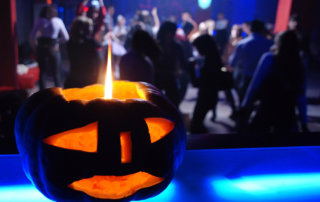 beginnings-treatment-centers-7-ways-to-have-a-sober-halloween-image-of-pumpkin-candle-with-halloween-dance-in-background