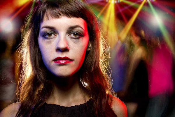 beginnings-treatment-centers-7-factors-that-contribute-to-drug-addiction-article-image-of-sad-woman-at-night-club