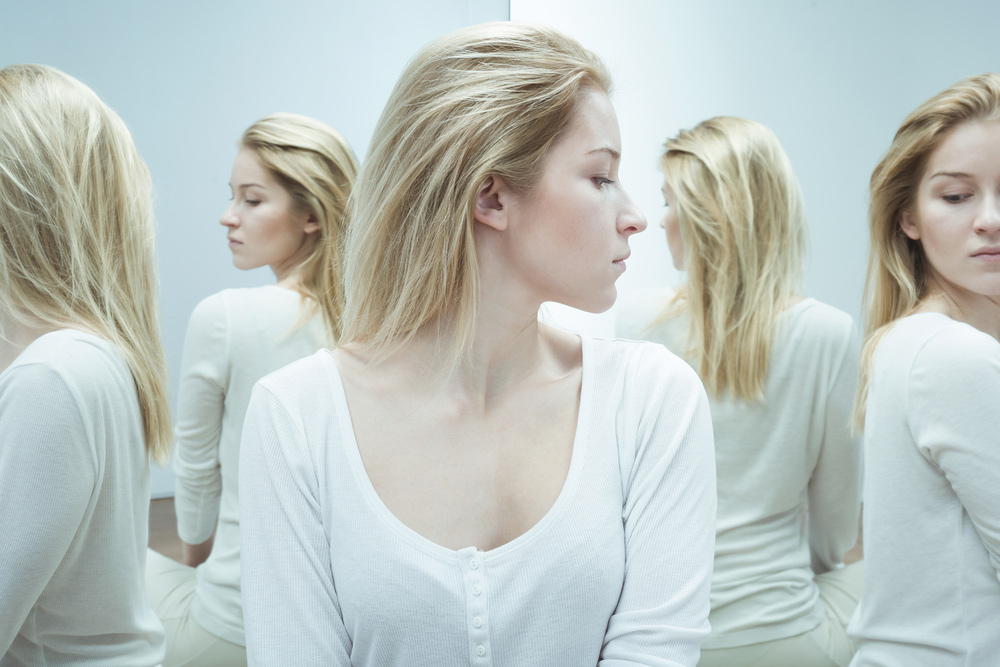 beginnings-treatment-centers-is-addiction-a-disease-or-a-choice-article-image-of-woman-with-mirror-images-of-herself-around-her