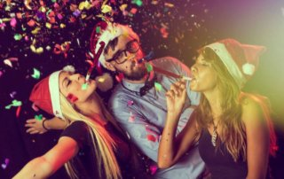 beginnings-treatment-how-can-i-get-through-the-holidays-sober-article-image-of--three-young-people-blowing-party-whistles-at-a-new-year-s-eve-party-337034882