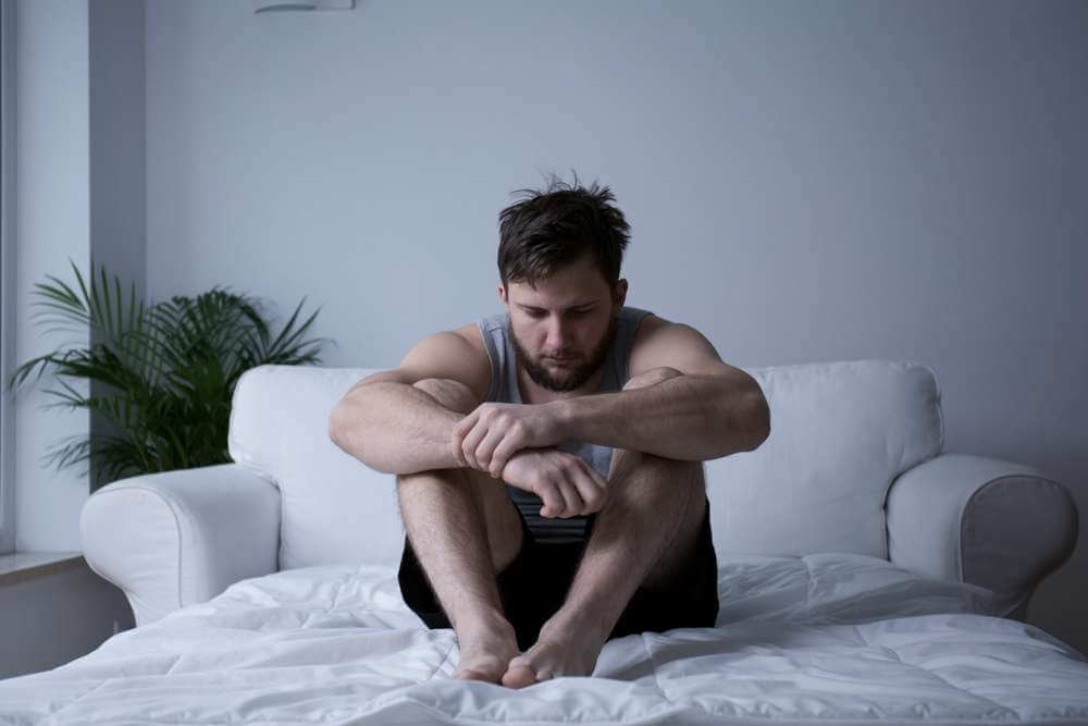 beginningstreatment-five-traits-of-an-addictive-personality-article-image-of-man-after-mental-breakdown-sitting-in-bed-312036692