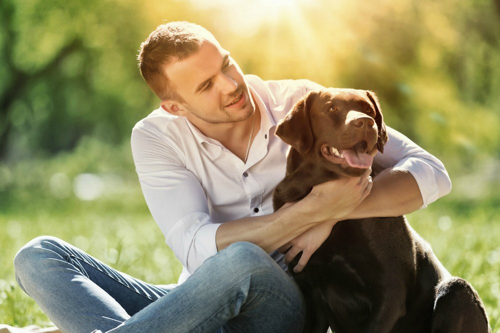 beginningstreatment-controlling-the-committee-in-your-head-article-photo-of-young-guy-with-retriever-on-walk-in-summer-park-295882361