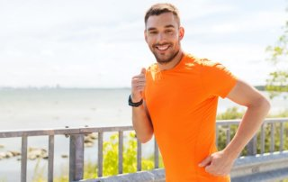 beginningstreatment-healthy-coping-mechanisms-for-your-recovery-article-photo-of-fitness-sport-people-technology-and-healthy-lifestyle-concept-smiling-young-man-with-heart-300552362