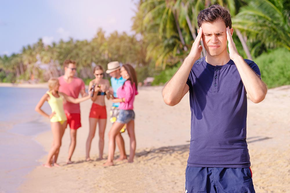beginningstreatment-5-tips-for-stopping-cravings-article-photo-stress-and-headache-young-man-feeling-bad-while-his-friend-enjoying-beach-party-519460792