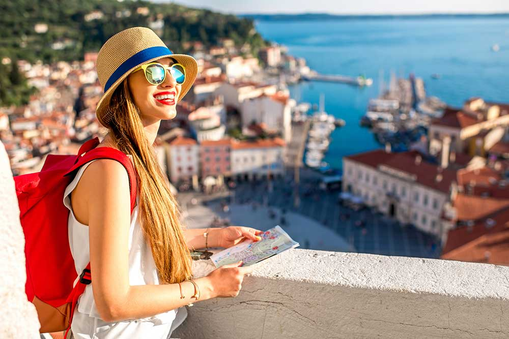 beginningstreatment-7-tips-for-staying-sober-while-traveling-article-photo-young-female-traveler-with-red-backpack-and-hat-enjoying-the-view-from-george-s-tower-on-piran-old-459099973