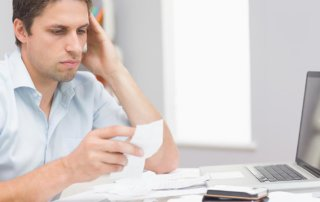 beginningstreatment-how-can-i-pay-the-bills-while-in-rehab-article-photo-worried-young-man-paying-his-bills-online-with-laptop-in-the-living-room-at-home-168091292