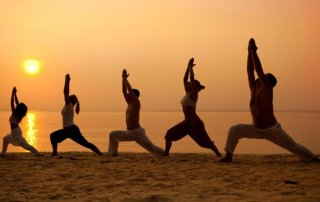beginningstreatment-what-is-refuge-recovery-article-photo-five-people-practising-yoga-at-the-beach-warrior-i-pose-227779006
