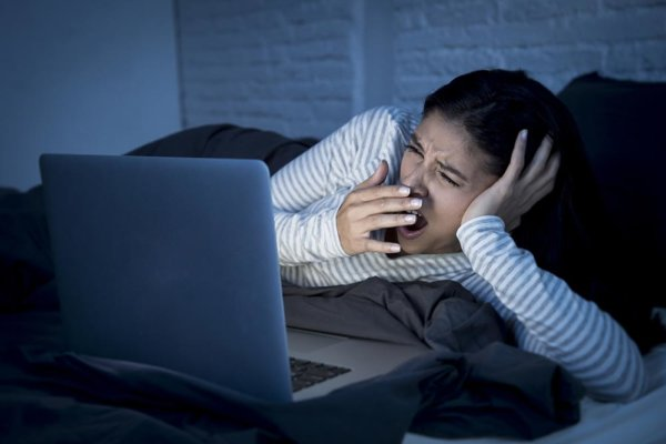 beginningstreatment-different-types-of-addictive-behaviors-article-photo-young-beautiful-hispanic-internet-addict-woman-in-pajamas-on-bed-at-home-bedroom-working-bored-and-570624208