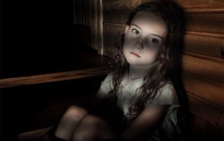 beginningstreatment-how-childhood-trauma-creates-adult-addicts-article-photo-depressed-girl-sitting-in-a-dark-hallway-in-home-321259787