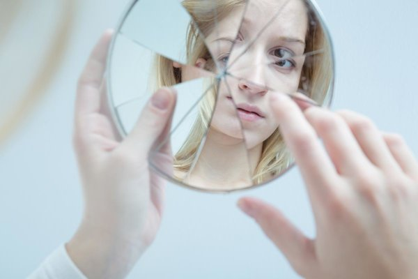 beginningstreatment-how-exercise-helps-you-stay-sober-article-photo-insecure-pretty-young-woman-holding-broken-mirror-356410439