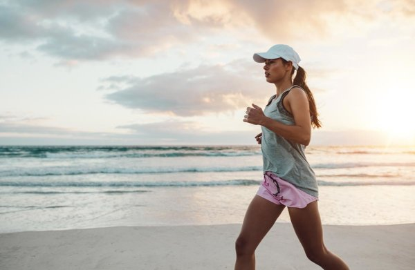 beginningstreatment-how-exercise-helps-you-stay-sober-article-photo-side-view-shot-of-beautiful-young-woman-in-sportswear-jogging-on-beach-female-runner-jogging-on-569531539