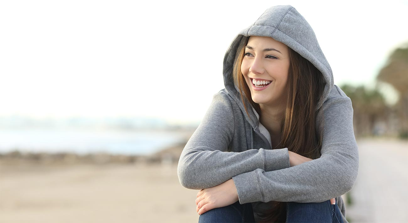 beginningstreatment-what-happens-in-rehab-article-photo-portrait-of-a-happy-teenager-girl-smiling-and-looking-at-side-outside-on-the-beach-376393804