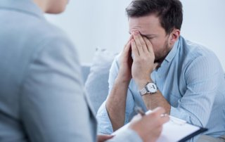 beginningstreatment-what-is-an-interventionist-article-photo-man-with-depression-crying-during-psychotherapy-session-338311319