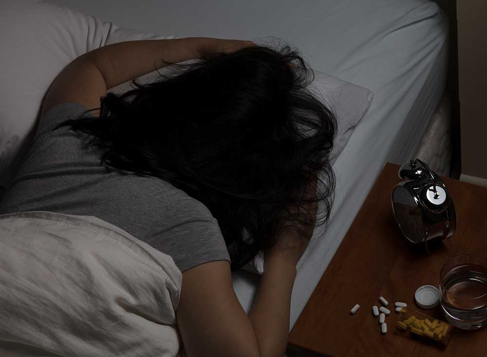 beginningstreatment-what-is-kratom-article-photo-woman-lying-face-down-in-pillow-with-pills-spilled-on-night-stand-depression-and-addiction-concept-598288520