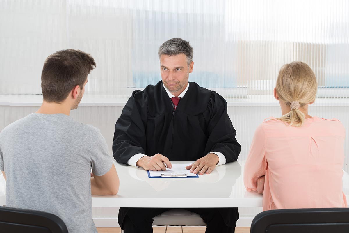 beginningstreatment-can-i-go-to-rehab-instead-of-jail-article-photo-mature-male-judge-sitting-in-front-of-young-couple-in-courtroom-328332065