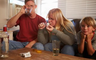 beginningstreatment-child-parent-share-addiction-article-photo-parents-sit-on-sofa-with-children-taking-drugs-and-drinking-193821536