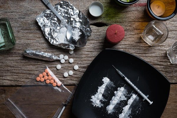 beginningstreatment-heroin-addiction-signs-symptoms-withdrawal-treatment-article-photo-alcohol-drugs-pills-on-a-wooden-background-683691733