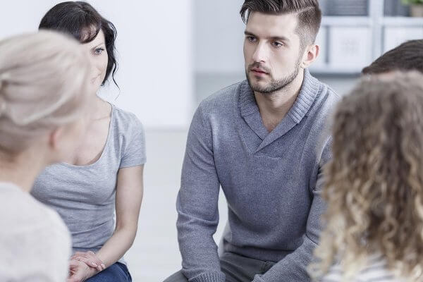 beginningstreatment-heroin-addiction-signs-symptoms-withdrawal-treatment-article-photo-unhappy-young-man-sitting-with-other-people-during-addiction-therapy-712952152