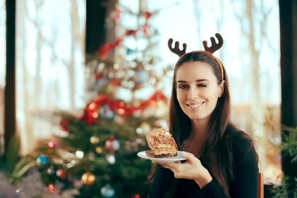 beginningstreatmentim-alone-can-i-stay-sober-over-the-holidays-article-photo-happy-woman-eating-cake-at-christmas-dinner-party-smiling-girl-eating-dessert-at-xmas-festivity-741241867