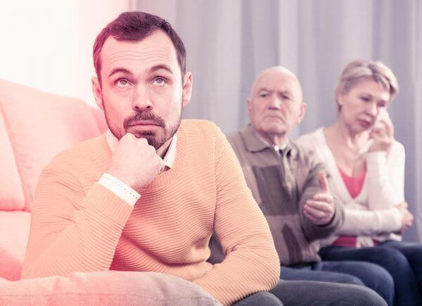 beginningstreatment-how-to-say-no-to-an-addict-you-love-article-photo-father-and-mother-having-disagreement-with-adult-son-at-home-672945142