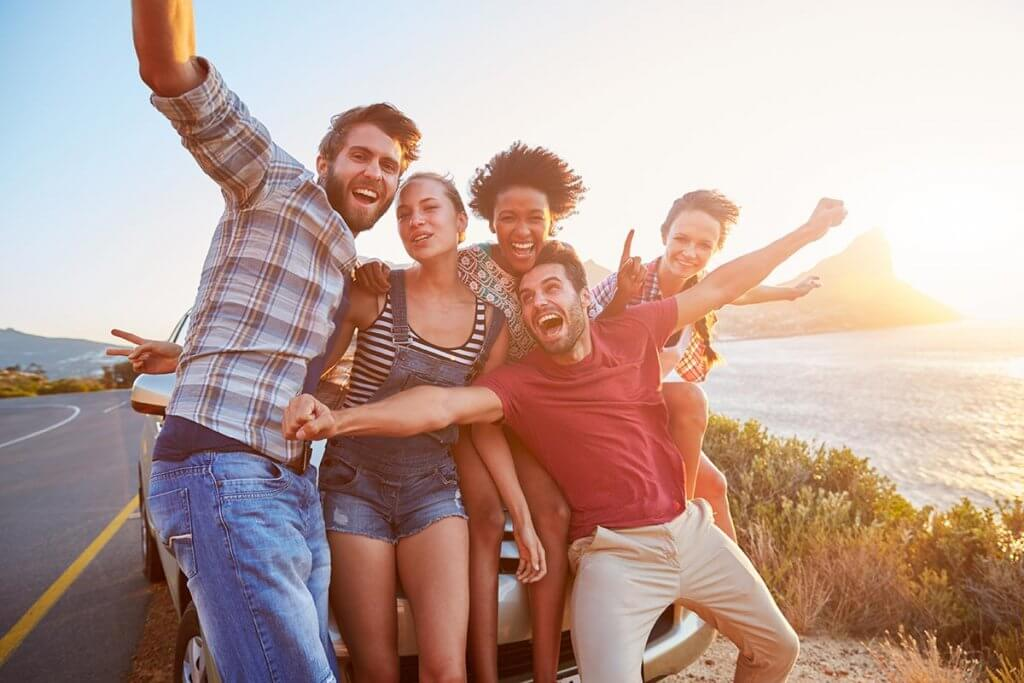 beginningstreatment-7-tips-for-a-successful-sober-vacation-article-photo-group-of-friends-standing-by-car-on-coastal-road-at-sunset
