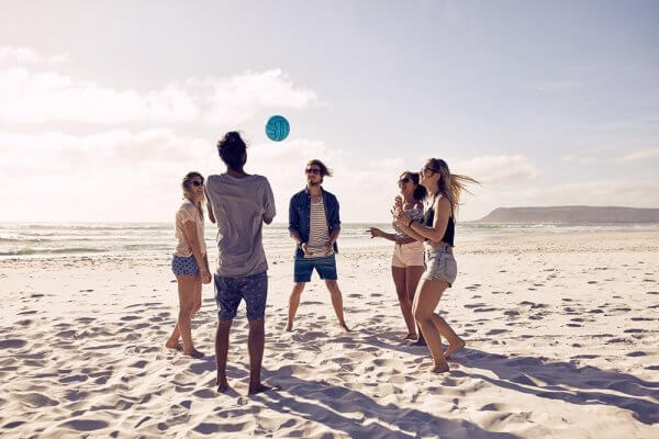 beginningstreatment-7-tips-for-a-successful-sober-vacation-article-photo-group-of-young-people-playing-with-ball-at-the-beach-young-friends-enjoying-summer-holidays