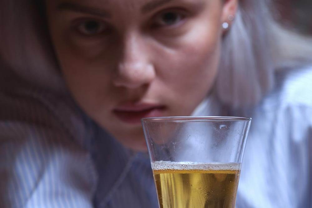 beginningstreatment-how-to-stay-in-recovery-if-you-work-around-alcohol-article-photo-closeup-portrait-of-young-drunken-female-sitting-at-the-table-with-beer-glass-woman