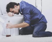 beginningstreatment-what-is-alcohol-poisoning-article-photo-drunk-man-with-wine-bottle-in-toilet-isolated-on-white