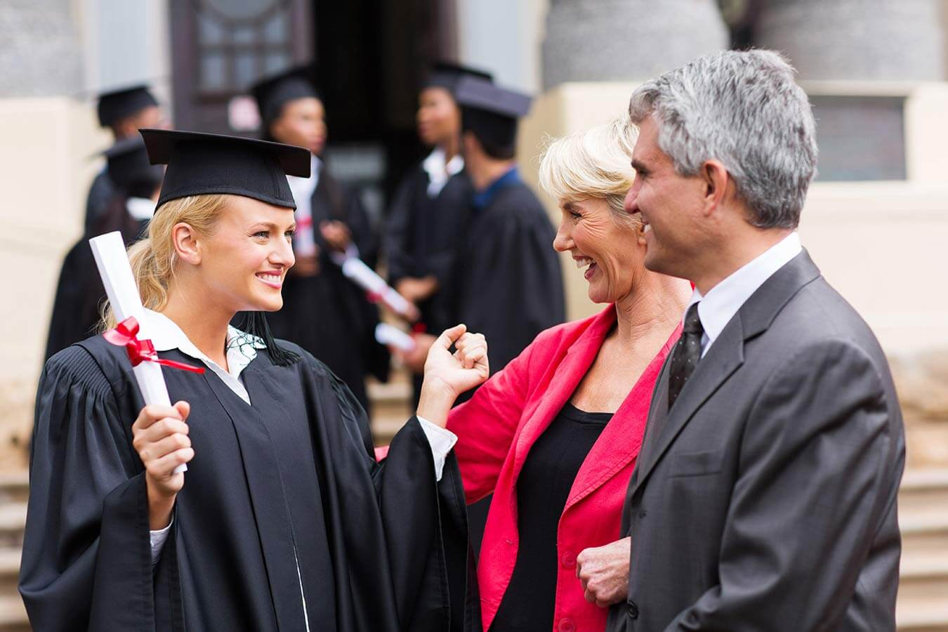 girl in cap and gown graduating from college holding her diploma with her happy parents congratulating her