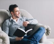 beginningstreatment-eight-tips-for-staying-positive-in-recovery-a-happy thoughtful man sitting on a chair