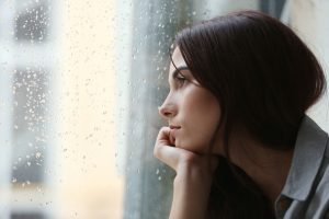 depressed-young-woman-near-window